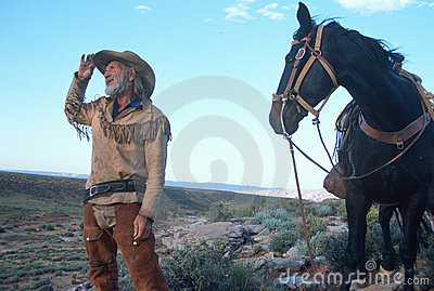 Cowboy and horse standing in desert Editorial Photo