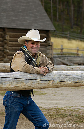 Cowboy Leans on Fence