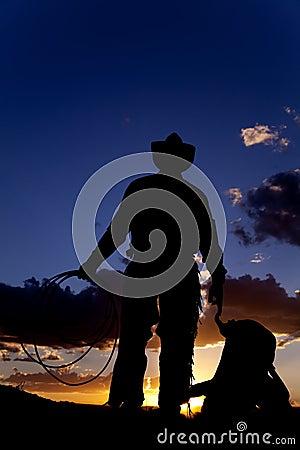 Cowboy with saddle on ground
