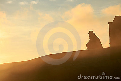 Cowboy silhouetted against the sunrise