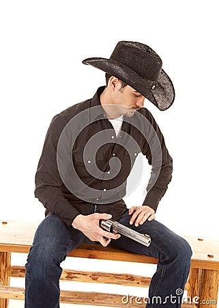 Cowboy sitting holding a gun