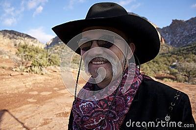 Cowboy sorridente con gli occhiali da sole in rocce rosse