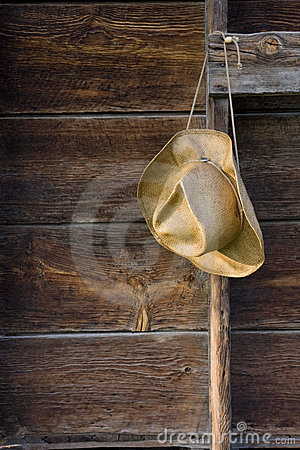 Cowboy straw hat against weathered wood