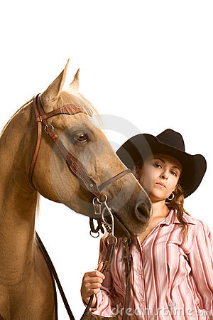 Cowgirl in hat holding her horse by bridle