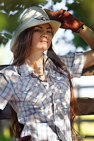 Cowgirl in stetson next to wooden fence