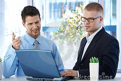 Coworkers discussing work in office