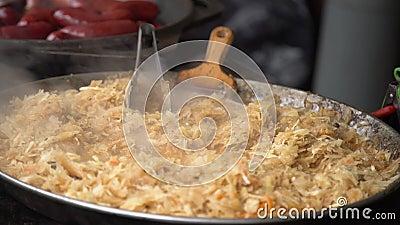 Cozinhando a couve dourada cozido em uma bandeja quente grande Alimento da rua para a venda em uma feira da cidade em Europa vídeos de arquivo