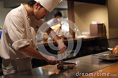 Cozinheiro chefe japonês que prepara a carne de Kobe Imagem Editorial