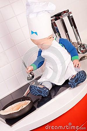 Cozinheiro chefe pequeno do bebê no chapéu do cozinheiro que faz panquecas