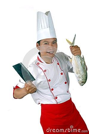 Cozinheiro chefe que prende uns peixes crus e uma faca de cozinha grandes