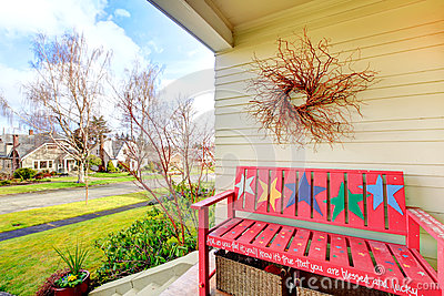 Cozy decorated porch with painted red bench and dry branch on th