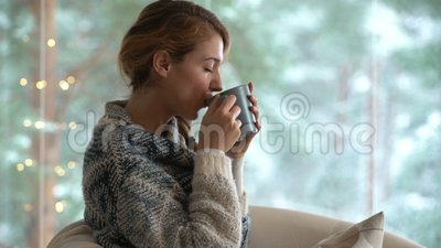 75049633ddb Young Happy Woman Drinking Cup Of Coffee Wearing Knitted Sweater Sitting  Home By The Big Window Stock Footage - Video of comfy, comfort: 104896762