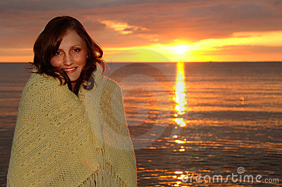 Cozy woman wrapped in blanket at sunset