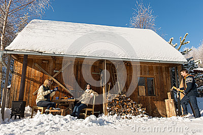 Cozy wooden cottage winter snow people outside
