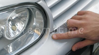 Cracked paint on car bumper. A man touches cracked paint of a car stock footage