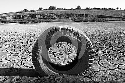 Dried land with cracks and tyre