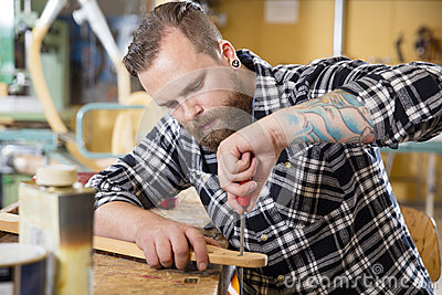 Craftsman files wooden guitar neck in workshop stock photo for Working man tattoo