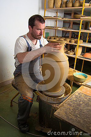 Craftsman making vase from wet clay on pottery whe