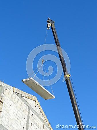 Crane lifting a part of a roof