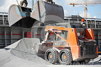 Crane loading cargo ship with gravel