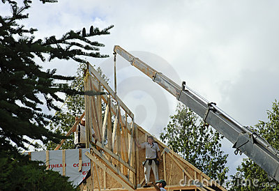 Crane for roof framing with workers Editorial Photo