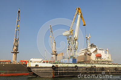 Cranes Loading a Cargo Ship with a Tanker Truck on