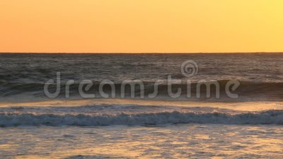 Waves and ocean mist at sunset stock footage
