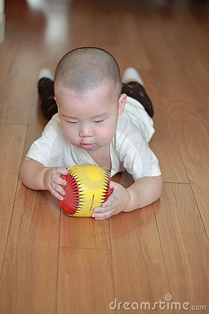 Crawling baby playing toy on floor
