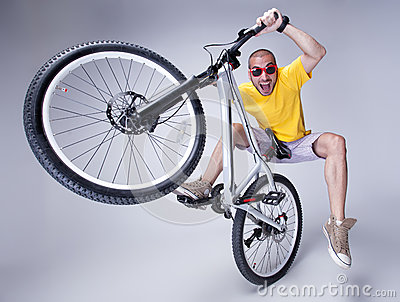 Crazy boy on a dirt jump bike on grey background -
