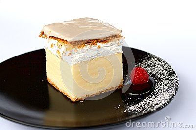 Creamy cake on black plate