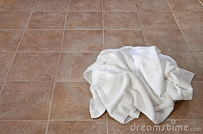 Creased white towels on ceramic floor
