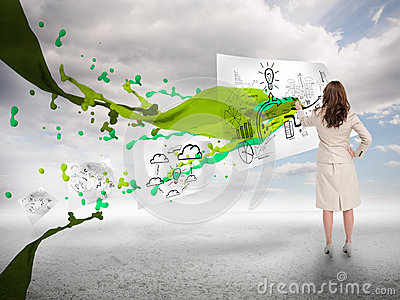 Creative businesswoman drawing on a paper next to paint splash