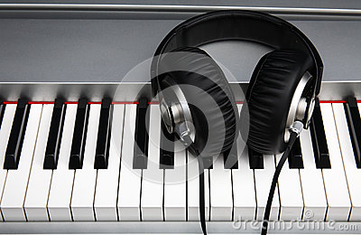 Creative concept of a digital piano keyboard with big black leather headphones