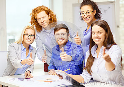 Creative team with papers showing thumbs up