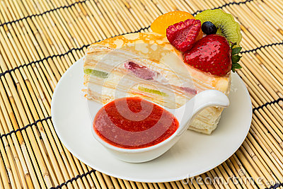 Crepes cake with orange, kiwi and strawberry sauce