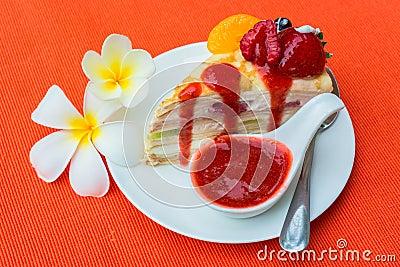 Crepes cake with orange, kiwi and strawberry sauce