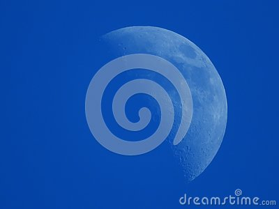 crescent moon in the blue afternoon sky Stock Photo