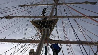 Crew members of Sailing Tall Ship climbing the mast in back light to enter the yards and prepare the sails in late afternoon stock video footage