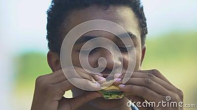 Criança afro-americana famosa comendo sanduíche delicioso, freio de almoço na escola vídeos de arquivo