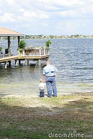 Criança com o pai no vertical do lago