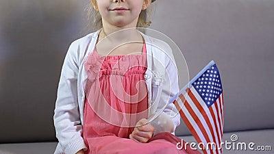 Criança fêmea bonito com a bandeira americana à disposição que senta o sofá, Dia da Independência video estoque