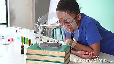 Criança misturada afro-americano que puxa o balanço da bola dos berços de um newton na sala de aula da ciência vídeos de arquivo
