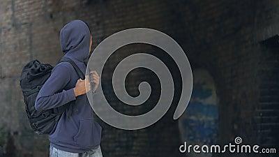 Criança negra pensada em capuz com mochila caminhando pelo perigoso subúrbio da cidade video estoque