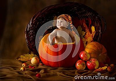 Criança no tampão dentro da abóbora. Colheita do outono