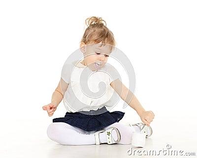 A criança pequena come o iogurte