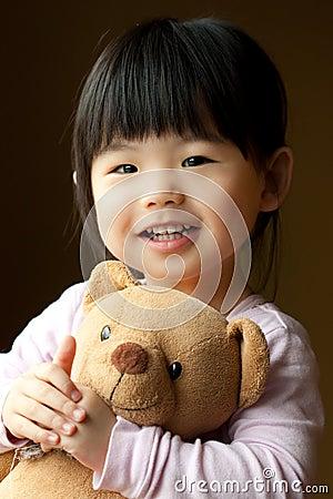 Criança pequena de sorriso com um urso de peluche