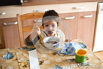 Criança que come o pequeno almoço