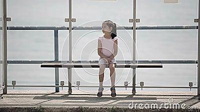 A criança que espera um ônibus na parada do ônibus olha ao redor e falta filme