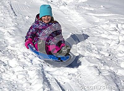 Criança que tem o divertimento no monte do trenó