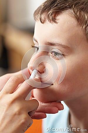 Criança que toma uma dose do pulverizador nasal